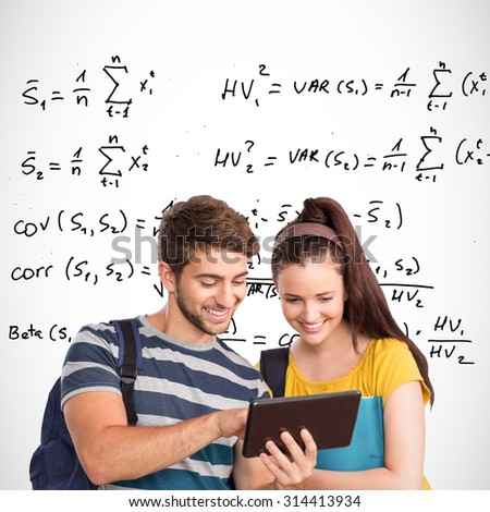 Happy students using tablet pc against maths equations - stock photo