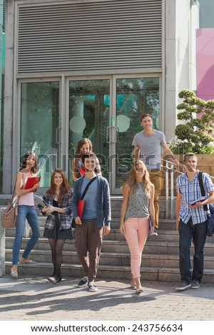 Happy students walking and smliling outside at the university - stock photo
