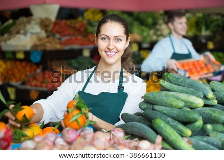happy stuff in apron selling sweet oranges, lemons and tangerines 