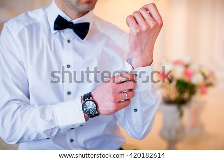 Happy stylish and elegant groom the morning of the wedding buttoning cuffs on his hands - stock photo