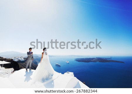 happy stylish asian bride and groom smiling and walking on background blue sea and sky in island Santorini - stock photo