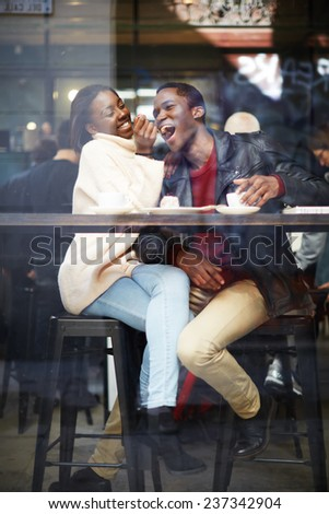 Happy stylish friends having coffee together, laughing young couple in cafe, having a great time together,view through cafe window, portrait of young couple in love at a coffee shop, people having fun - stock photo