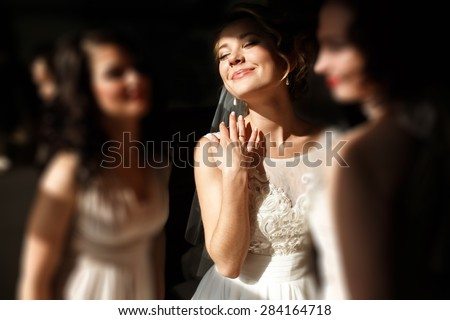 happy stylish gorgeous blonde bride with bridesmaids on the background  hotel room - stock photo