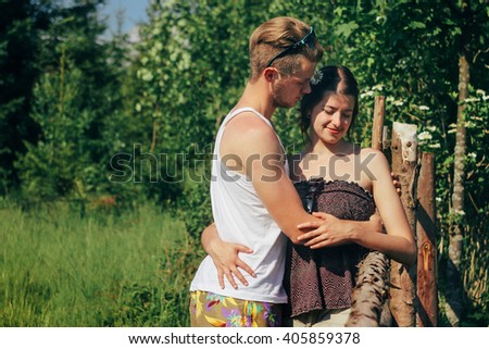 happy stylish hipster couple hugging and smiling on background mountains in summer