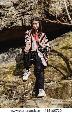 happy stylish hipster woman traveling, sitting on cliff in mountains with photo camera and smiling