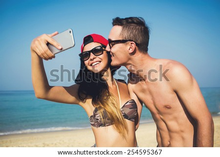 Happy stylish multiracial couple on honeymoon travel in Phuket beach coast, Thailand, taking selfie portrait photo with smartphone camera.