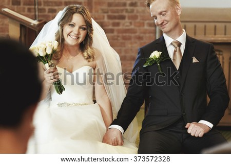 Happy stylish newlyweds holding hands in the church  on the wedding ceremony