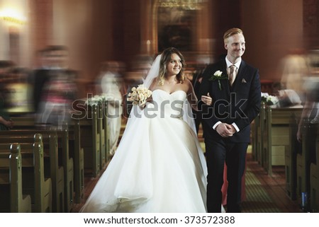 Happy stylish newlyweds holding hands in the church  on the wedding ceremony - stock photo