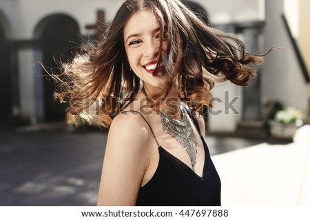 happy stylish woman waving hair in sunlight at old european city street, luxury look, space for text, moment of carefree and true happiness - stock photo