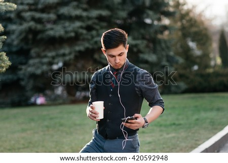 Happy stylish young man using application on his phone - stock photo