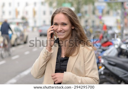 Happy stylish young woman chatting on her mobile phone as she stands in an urban street smiling with delight as she listens to the conversation