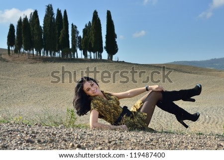 Happy stylish young woman in country field. Tuscan, Italy - stock photo