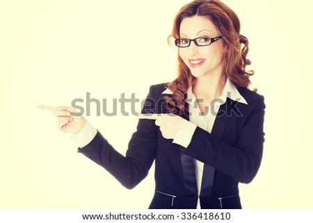 Happy success business woman pointing on copy space - stock photo