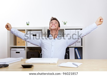 Happy successful business man cheering with clenched fists in office