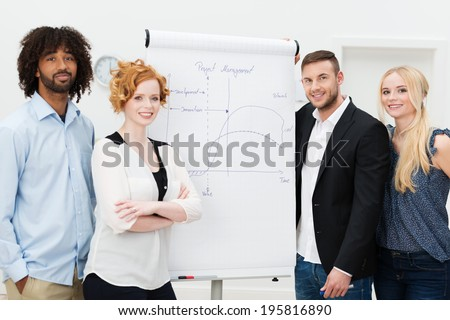 Happy successful business people standing grouped around a flip chart during an in house training session and presentation, men and women present