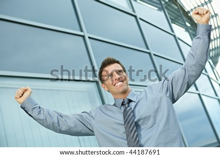 Happy successful businessman raising arms outdoor, smiling. - stock photo