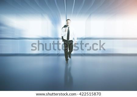 Happy successful businessman walking in blurry interior - stock photo