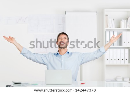 Happy successful businessman with arms raised sitting at office desk - stock photo