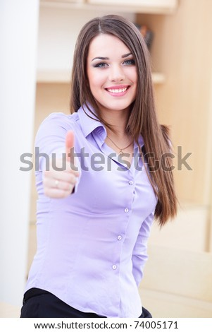 Happy successful businesswoman giving you thumbs up gesture - stock photo