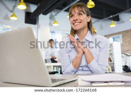 Happy Successful  businesswoman in office, with arms up