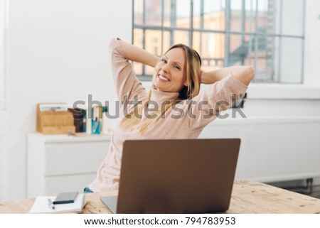 Happy successful businesswoman relaxing in her chair at the office with her hands behind her neck and a big smile