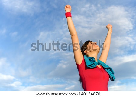 Happy successful fitness woman raising arms and winning after exercising. Success in sport training concept. - stock photo