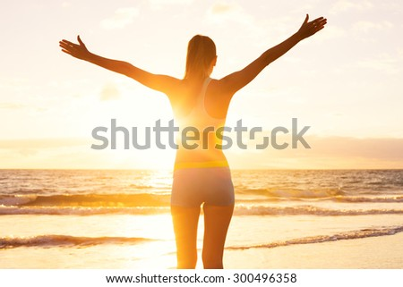 Happy successful fitness woman raising arms to the sky at sunset. Success, celebrating goals and achievement. Healthy Active Lifestyle.  - stock photo