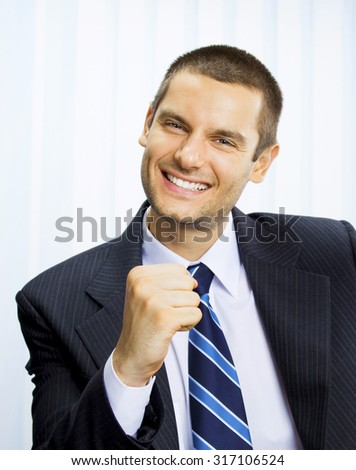 Happy successful gesturing businessman at office - stock photo