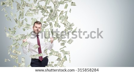 Happy successful manager or businessman is getting benefits from his job. Dollar note are falling down from the ceiling. Concrete background. - stock photo