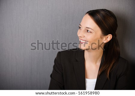 Happy successful professional woman with a lovely broad smile looking sideways, head and shoulders portrait on grey with copyspace - stock photo