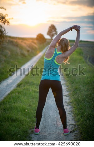 Happy successful sportswoman raising arms to the sky on golden back lighting sunset summer. Fitness athlete with arms up celebrating goals after sport exercising and working out outdoors. - stock photo