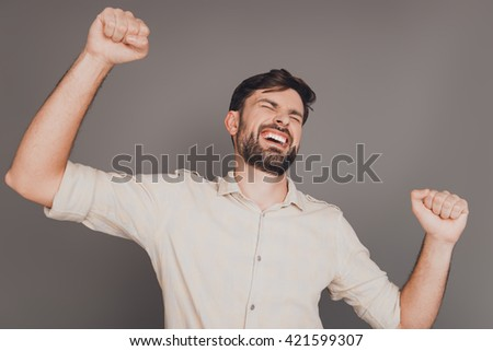 Happy successful young winner triumphing with raised hands