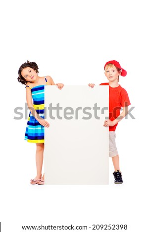 Happy summer children in bright clothes stand together and hold white billboard. Copy space. Isolated over white. - stock photo
