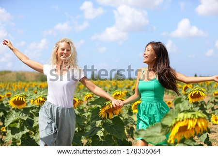 Happy summer girls laughing fun in sunflower field in spring. Cheerful multiracial girlfriends running joyful and smiling holding hands in countryside. Asian and Caucasian woman. - stock photo