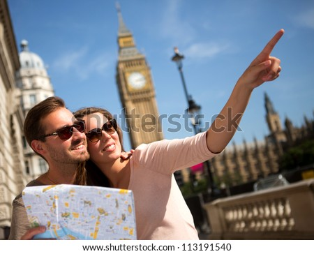 Happy summer tourists in London holding a map - stock photo