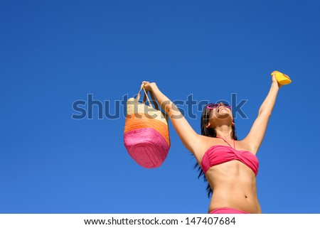 Happy summer vacation. Blissful bikini woman ready for sunbathing protecting skin with sunscreen or suntan lotion. Sexy caucasian girl raising arms to clear blue sky enjoying summertime, heat and sun. - stock photo