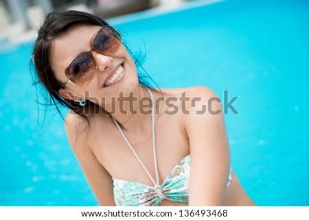Happy summer woman by the swiming pool in bikini - stock photo