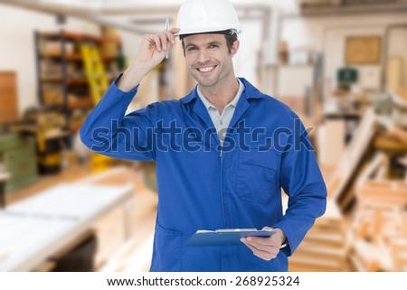 Happy supervisor wearing hard hat while holding clip board against workshop - stock photo