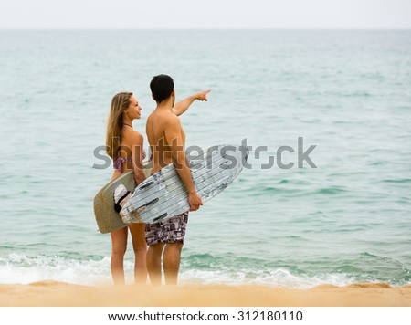 Happy surfers couple standing with surfboards on the sandy beach