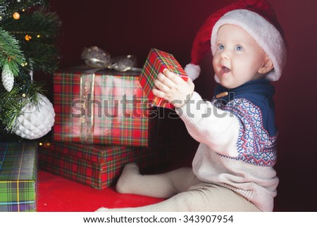 Happy surprised baby holding gift box or present at Christmas night, eve! Kid dressed in red Santa hat. Xmas and New Year holiday! - stock photo