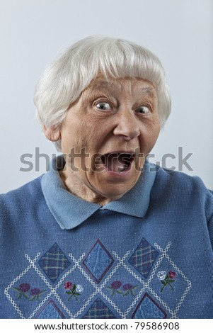 Happy surprised senior woman head and shoulders portrait - stock photo