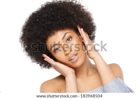 Happy surprised young African American woman in a sexy off the shoulder top looking at the camera with an excited look and her hands raised to her head - stock photo