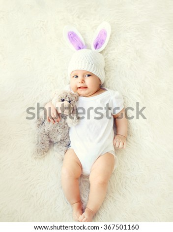 Happy sweet baby in knitted hat with a rabbit ears and teddy bear toy lying on bed, top view - stock photo
