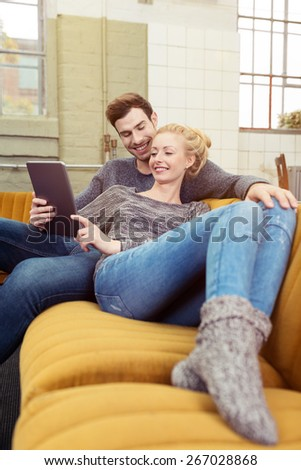 Happy Sweet Couple Sitting on the Brown Couch with Tablet Computer While Girlfriend Leaning to her her Boyfriend. - stock photo