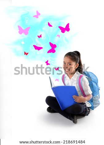 Happy sweet little Hispanic school girl smiling reading magic book with wonderful stories and tales represented by pink  butterflies flying out the pages in children imagination concept - stock photo