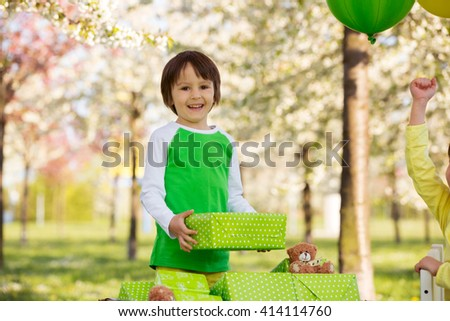Happy sweet preschool children, friends and relatives, celebrating fifth birthday of cute boy, outdoors in blooming tree garden, springtime, late afternoon. Birthday kid preparing to open presents - stock photo
