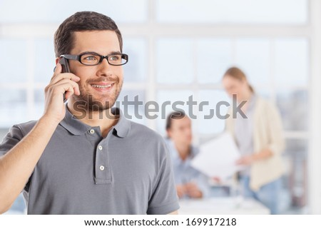 Happy talk. Cheerful young businessman in casual wear talking on the phone and smiling while his colleagues communicating on the background - stock photo