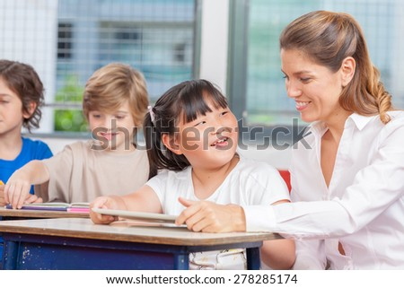 Happy teacher and multi ethnic classroom learning and having fun. - stock photo