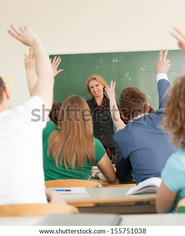 Happy teacher looking at her class students