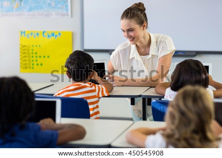 Happy teacher showing digital tablet to boy in classroom